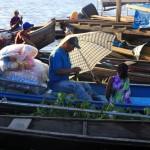 Vader wordt uit de zon gehouden in de haven van het Braziliaanse Tabatinga